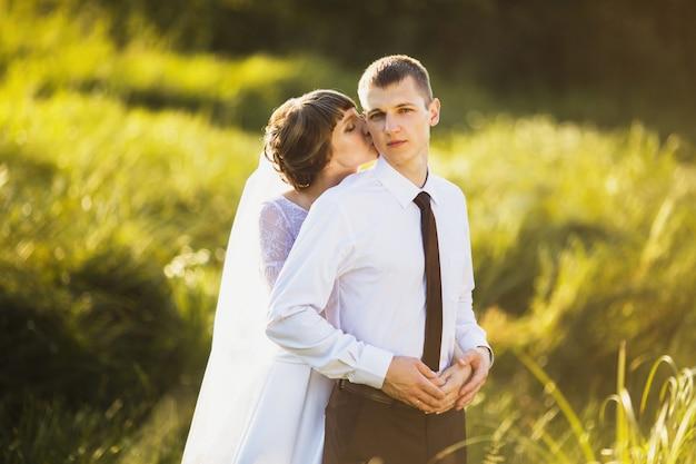 日光と自然に結婚式のカップル。男と女の間の愛。ウェディングドレスの花嫁。スーツの新郎。美しいウェディングブーケ。