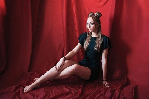 Блондинка с большими голубыми глазами, похожими на эльфа, длинными седыми волосами в пучок, девушка с прической и макияж в зеленом платье на красном фоне