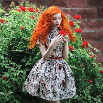 赤いバラとブッシュと花柄のドレスに赤い巻き毛の女性。淡い肌、青い目、明るく珍しい外観、赤い唇、庭の細い腰をした赤い髪の少女。