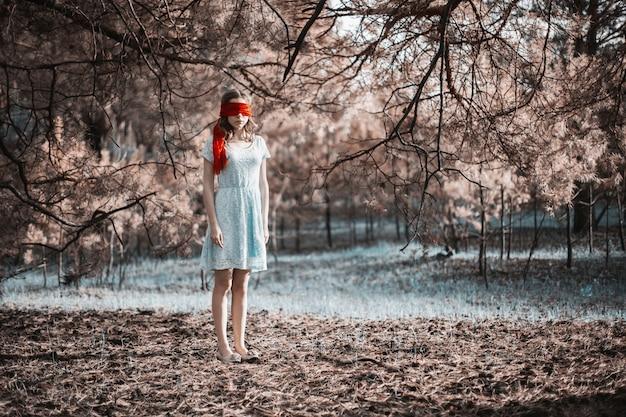Рабство. очень милая молодая девушка с завязанными глазами красной лентой. внешность куклы. женщина с каштановыми волосами в бирюзовом платье на природе. длинные волосы. естественный свет. модель позирует на природе. похищение людей