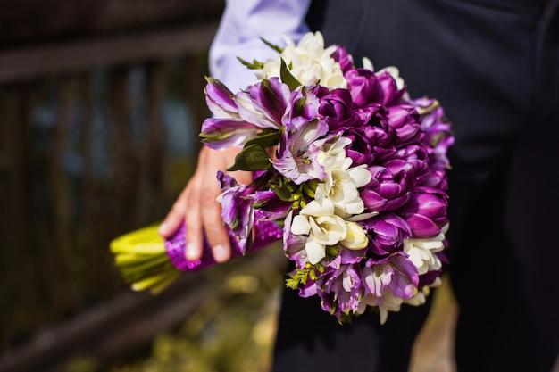 男の手に花の花束、花の花束を保持している実業家の手に新郎新婦の白と紫の花の束