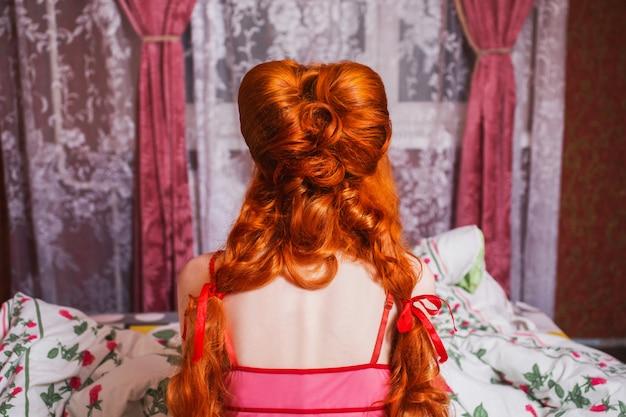 Женщина с длинными рыжими вьющимися волосами собралась в косы и ночную рубашку в постели под одеялом. рыжая девушка сидит обратно в камеру в спальне на кровати. высокая прическа