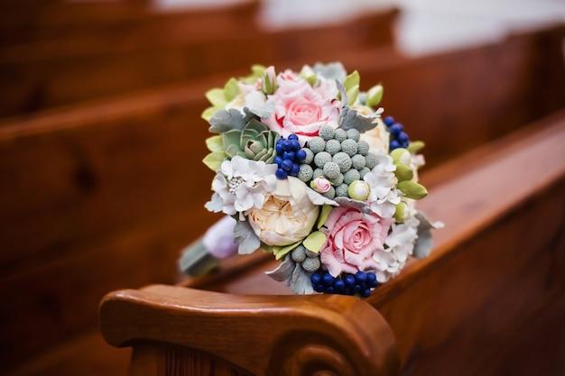 Искусственный свадебный букет на церковном интерьере