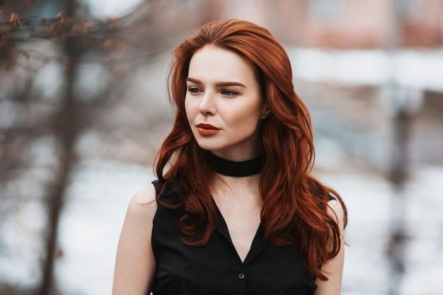 黒い服を着た長い赤い髪を持つ魅力的な女の子の肖像画。黒のドレスと冬、秋の自然の背景にポーズをとって長い黒い手袋の女性。女性のストリートスタイル。美しくエレガントなモデル