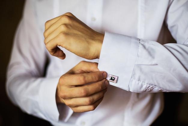 男はシャツとカフリンクスを着て、正しい服装、着こなし、男のスタイル、新郎の結婚式、結婚式の準備、スタイルの感覚、袖の修正