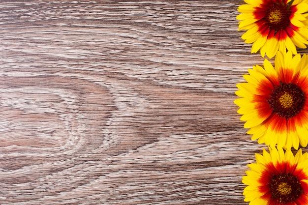 黄色の花は木製の背景にあります。テキストとデザインのためのスペース。