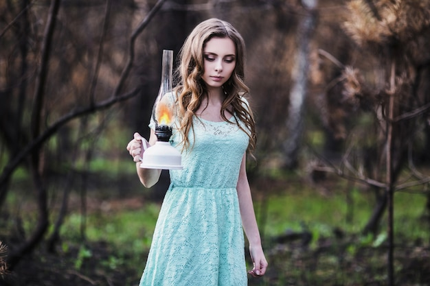 灯油ランプを持つ非常にかわいい若い女の子。人形の外観。自然にターコイズブルーのドレスに茶色の髪を持つ女性。長い髪。自然光。自然でポーズをとるモデル。手にランプ。森で迷子