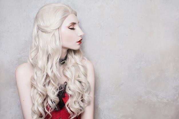 Роскошная белокурая женщина с красивыми длинными белыми волосами и красными губами на сером фоне.