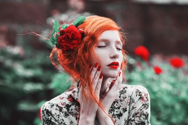 赤いバラの茂みの背景に花柄のドレスに赤い巻き毛の女性。淡い肌、青い目、明るく珍しい外見、赤い唇、庭の細い腰を持つ赤い髪の少女。