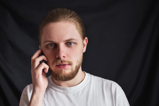 Брутальный мужчина в анфас с бородой разговаривает по мобильному телефону