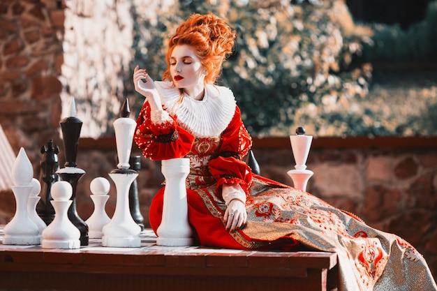 赤の女王はチェスをしている。シックなヴィンテージのドレスを着た赤髪の女性。ファッション写真