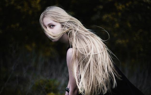 Блондинка с очень длинными волосами на темном фоне. женский портрет. концептуальная фотография. лицо девушки покрыто волосами.