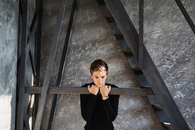Молодой парень в черной рубашке с часами на руке в темной комнате с естественным освещением. эмоциональный портрет. яркий показ эмоций. концептуальная фотография. талантливый актер.