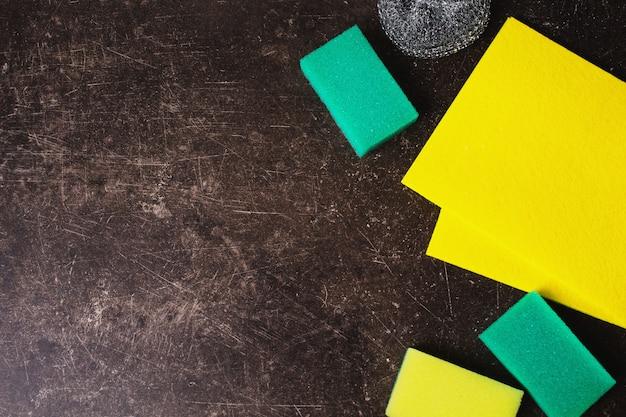 黄色のナプキン、暗い大理石の背景に色と金属のスポンジ。衛生・食器洗い用品