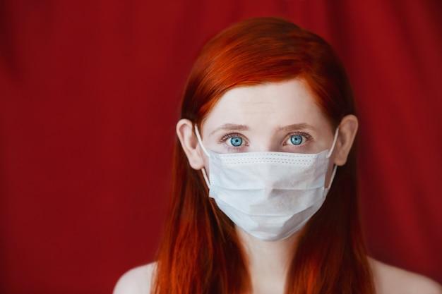 赤い背景、女医、強烈な表情、ヨーロッパ、耳の女の子の医療マスクを持つ赤い髪の少女