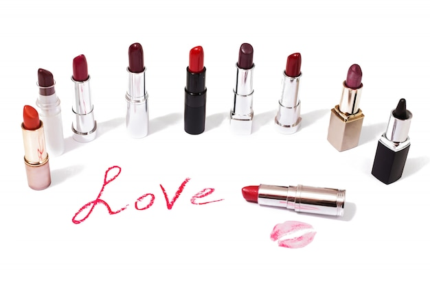 口紅が分離されました。女性のリップペンシル。紙に唇のキス。口紅で書かれた愛という言葉。