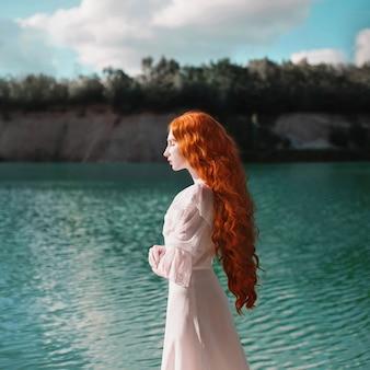 Красивая рыжеволосая женщина в роскошном ренессансном платье на фоне озера с голубой водой