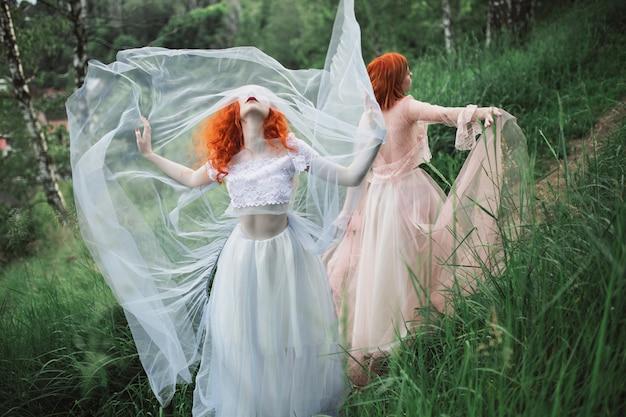Две рыжеволосые девушки в свободных платьях из тюля на фоне летнего оврага. две стройные модели позируют на природе