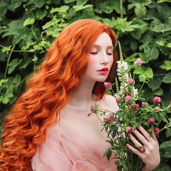 Красивая прерафаэлитная девушка с вьющимися рыжими волосами с развевающимся платьем из тюля на фоне папоротника