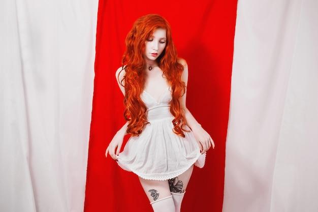 赤白の背景に白いドレスを着たスリムなウエストの赤い髪の少女。フェチモデル。