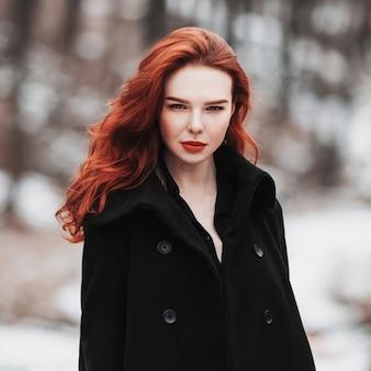 黒い服を着た長い赤い髪を持つ魅力的な女の子の肖像画。冬、秋の自然の背景にポーズをとって黒いコートを着た女性。女性のストリートファッションのスタイル。美しくエレガントなモデル