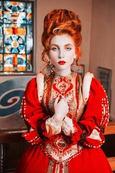 Рыжеволосая девушка с голубыми глазами в красном платье. королева с высокой прической. старинное изображение. женщина с бледной кожей