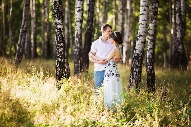 Красивая девушка с темными волосами и карими глазами с венком на голове в летнее платье, обнимая мужчину в белой рубашке на зеленом фоне. влюбленная пара в лесу в солнечный день. любить друг друга