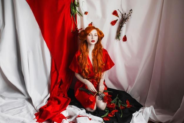 青い目と赤いコートの薄い肌の赤い髪の少女。花を持つ女性。髪をカール。白い背景の上のゴシック様式。