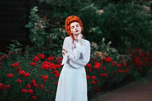 Красивая рыжеволосая девушка с высокими волосами в старом белом платье в парке. викторианская эпоха. исторический костюм. белая королева. замок принцессы