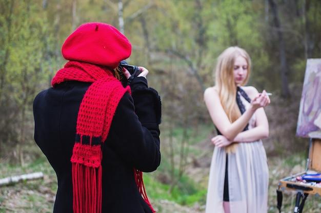 アウトドア、ライフスタイル。手にタバコを持つ長い髪の少女。女の子の写真家は美しいブロンドを捕らえます。写真家の作品。春に屋外で撮影する