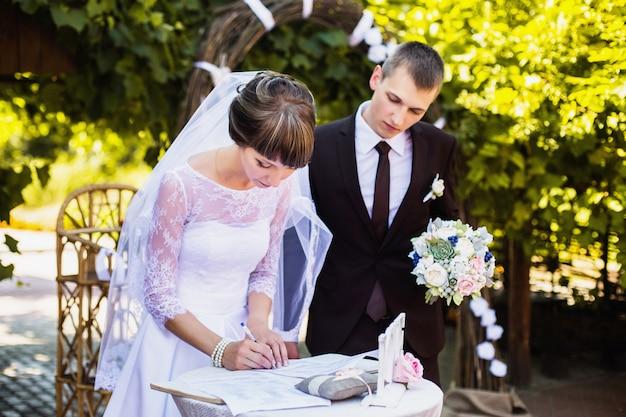 アーチの背景に白いドレスを着た新郎新婦。結婚式。幸せな家族