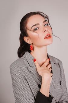 白い背景の上のコートのファッションブルネットの少女の肖像画。女性の健康。赤い爪を持つ官能的な日焼けした女性。赤い唇とブルネット。官能的な肖像画。赤い爪のマニキュア。美容ウェルネス。日焼け肌