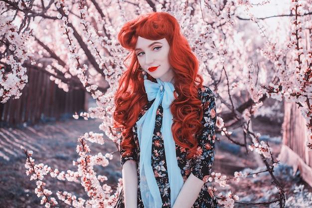 春の花の庭で幸せな女笑顔。バレンタインデーの背景。ドレスの魅力的な女性。笑顔。自然の背景の女性。幸せな赤毛モデル。春の花の背景。バレンタインコンセプト