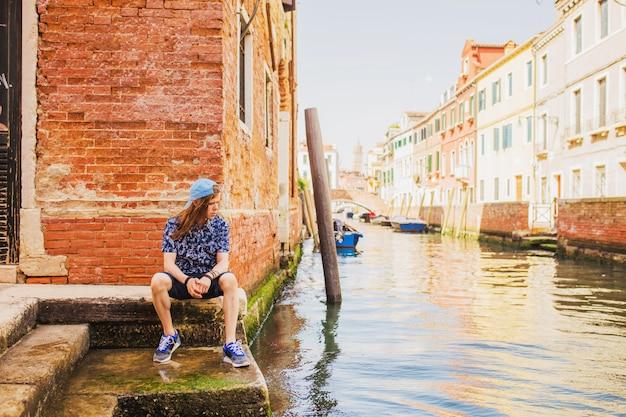 ヴェネツィアの運河の背景に長い髪を持つスタイリッシュな男が座っています。イタリアへ旅行します。ヴェネツィアの水の家。ショートパンツとシャツの若い男。イタリアの観光客
