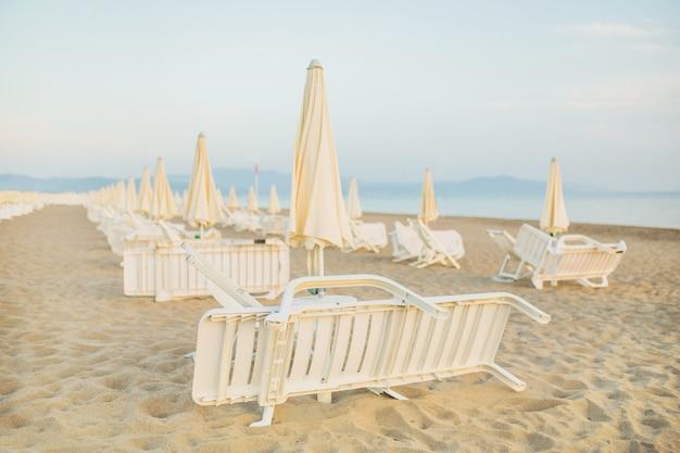 ビーチの朝。海岸で夜明けに会います。夏の背景。リラックスする場所。海でのレジャー。傘と椅子のビーチ。美しい朝の風景。ヨーロッパ旅行。サマーリゾート