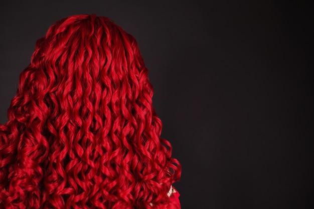 輝きの長いウェーブのかかった髪の赤毛の女の子。赤いかつら。自然の美。変態髪の少女。ボリュームのある赤いかつら。サロンでのぬりえ。輝きの髪型。赤毛の女性。