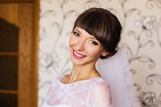 花嫁の朝。結婚式。白いドレスとベールの女の子。服を着る。女性のポートレート