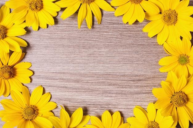 木製の背景に明るい夏の黄色い花のフレームです。デザインのための場所。黄色の花びら。