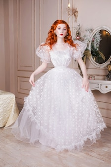 彼女の耳に白い真珠のイヤリングと白いビンテージのウェディングドレスの長い赤い巻き毛を持つ女性。淡い肌、青い目、豪華な寝室の明るく珍しい外観の赤い髪の少女