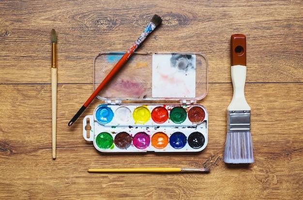 Художественная белка кисти, трубки масляных красок и акварели на деревянном фоне. палитра двадцать четыре цвета. набор художественных подержанных инструментов