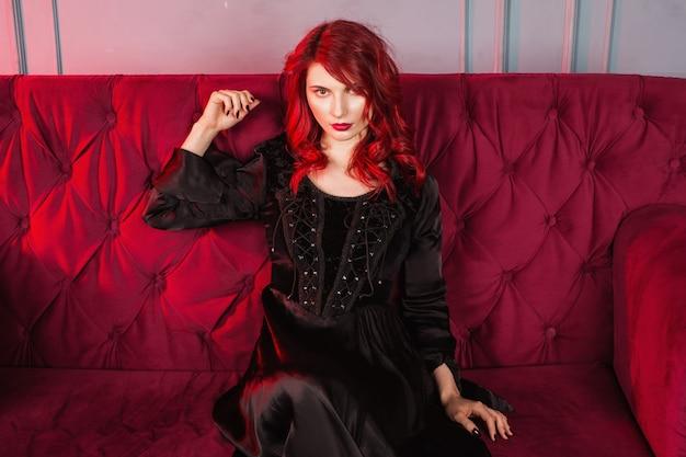 赤い髪とナチュラルメイクと淡い肌の美しい少女。赤いソファに座っている黒のレトロなドレスを着た女性。モデルのポーズ。珍しい外観。陰湿な邪悪な魔女の女性。