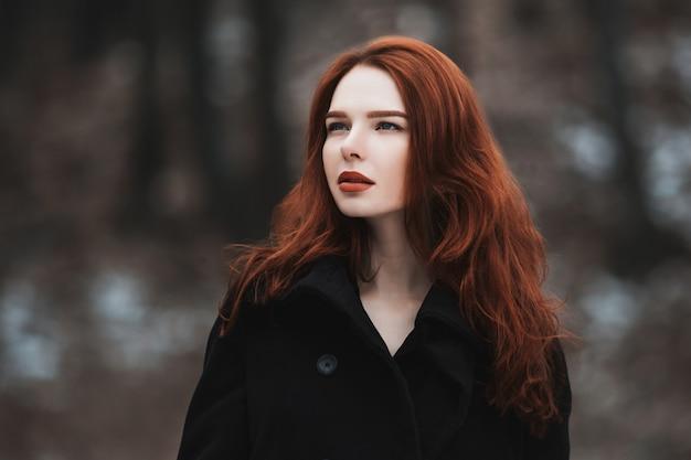 黒い服を着た長い赤い髪を持つ魅力的な少女の肖像画。黒いコートのポーズの女性