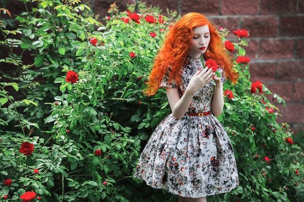 花柄の赤い巻き毛を持つ女性は、赤いバラの茂みをドレスアップします。
