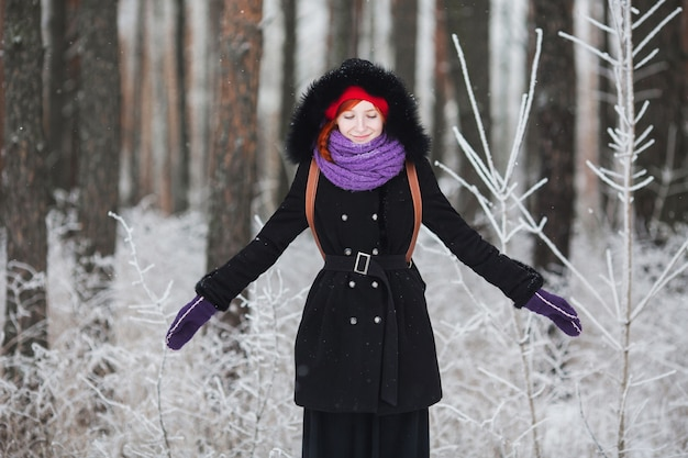 Рыжая девушка в шубе радуется зиме, мужчина стоит на снегу, девушка в зимнем лесу, люди смеются, радуются, хорошее настроение, счастье, девушка смеется