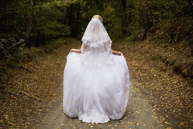後ろからの花嫁、女の子のウェディングドレス、森の花嫁、森のプリンセス、女性の後ろからのウェディングドレス、裾のドレス、ベール、結婚式の写真撮影、髪型の写真