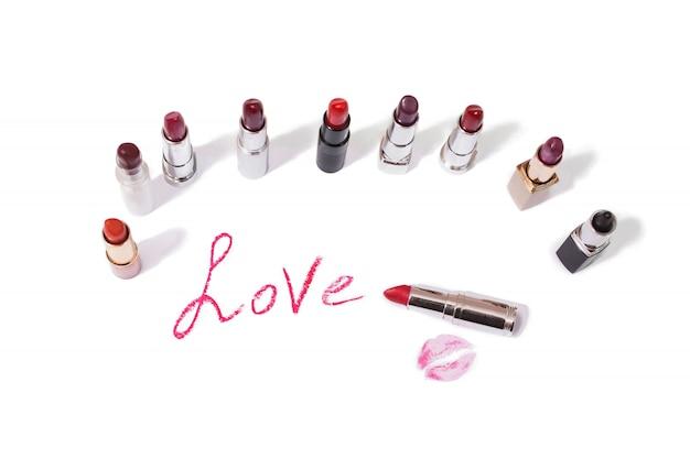 白で隔離の口紅。女性のリップペンシル。紙に唇のキス。口紅で書かれた愛という言葉。