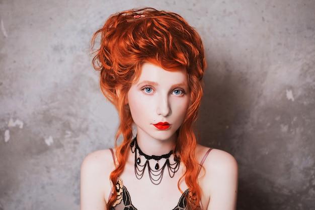 Женщина с рыжими волосами в ночной рубашке. рыжеволосая девушка с бледной кожей и голубыми глазами с яркой необычной внешностью с колье на шее на серой стене.