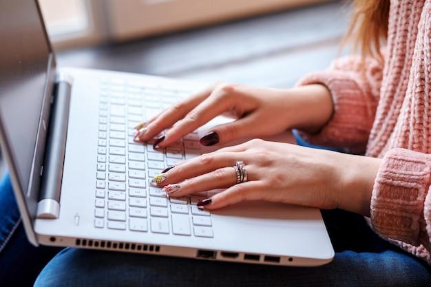 Руки белой женщины с маникюром на клавиатуре ноутбука. работать или учиться дома. фрилансер, удаленный работник, студент. обучение онлайн.