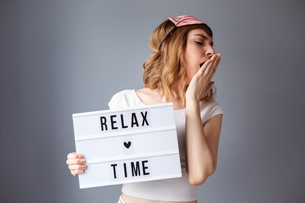 リラックス時間動機パネルを持つ魅力的な女性はあくびをしています。