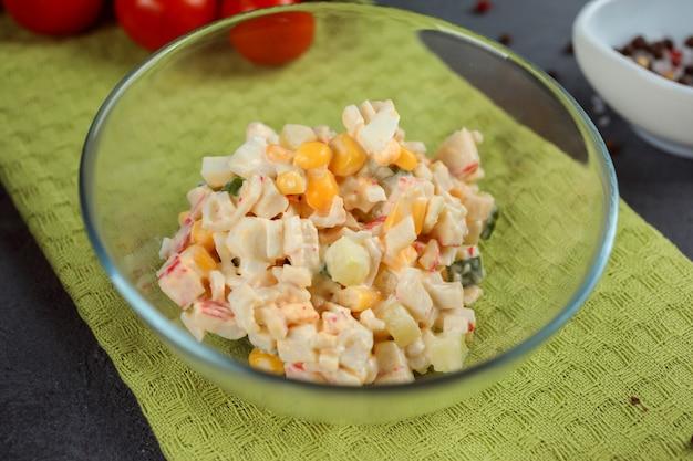 Русский традиционный салат с кукурузой, яйцом и крабовым мясом, заправленный майонезом на зеленом полотенце.